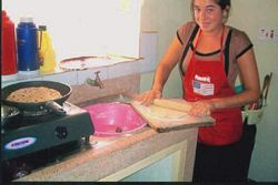 A Volunteer helps in cooking chapatis.