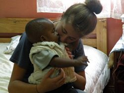 Emily from USA cuddling a baby -  Volunteer in East Africa